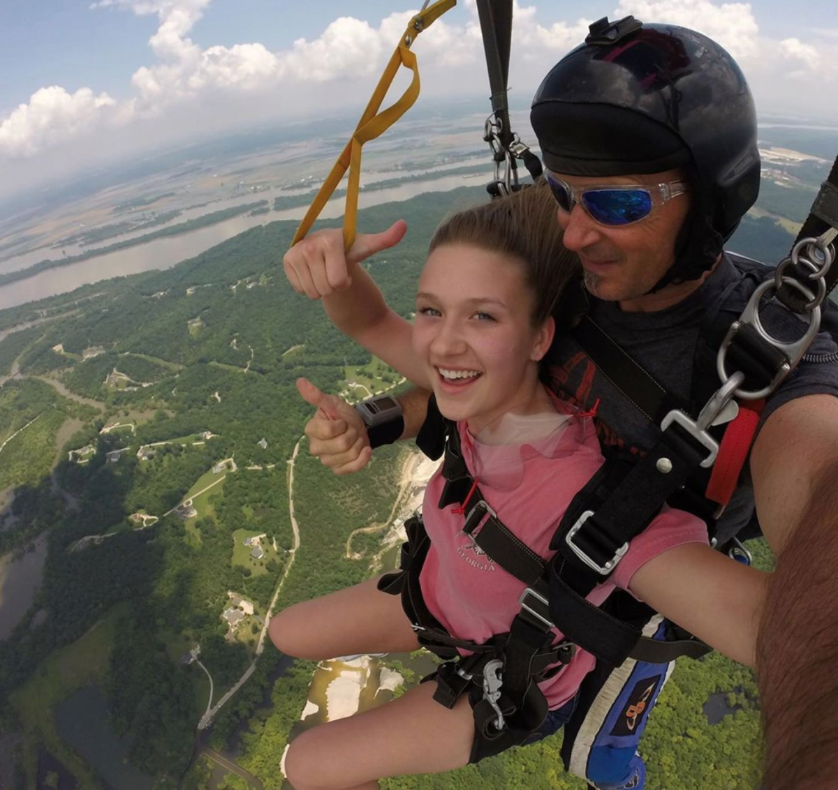Girl smiling while parachuting down after a tandem skydive at Skydive St Louis