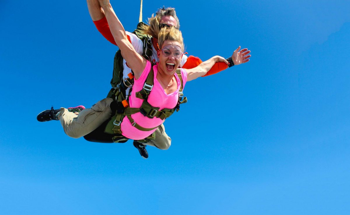 Woman smiling and laughing while tandem skydiving at Skydive STL