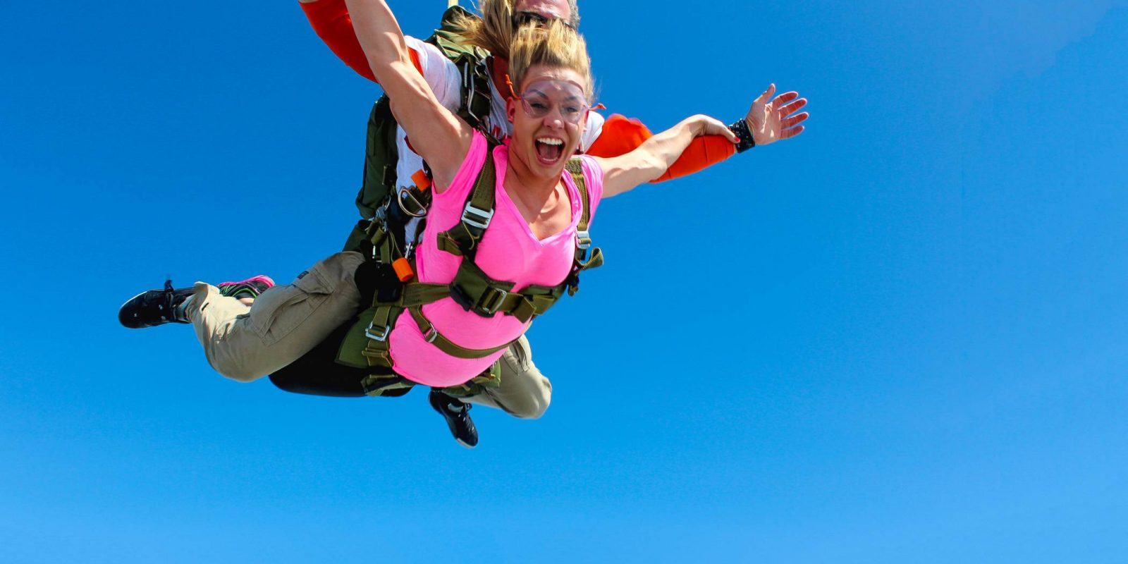 Woman tandem skydiving for the first time with an instructor