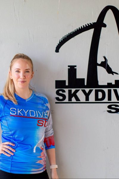 kerri office manager wearing blue jersey and pants in front of white wall smiling with hands on hips