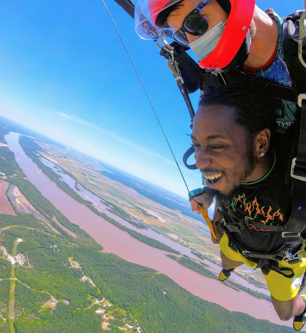 Man smiling with joy as he prepares to land after a tandem skydive with Skydive St Louis
