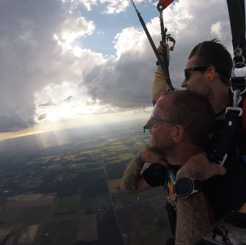 Man tandem skydiving with instructor and smiling near St. Louis Missouri