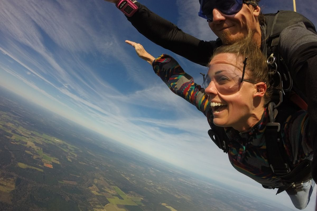 A woman is smiling from her first time tandem skydiving over St. Louis, MO