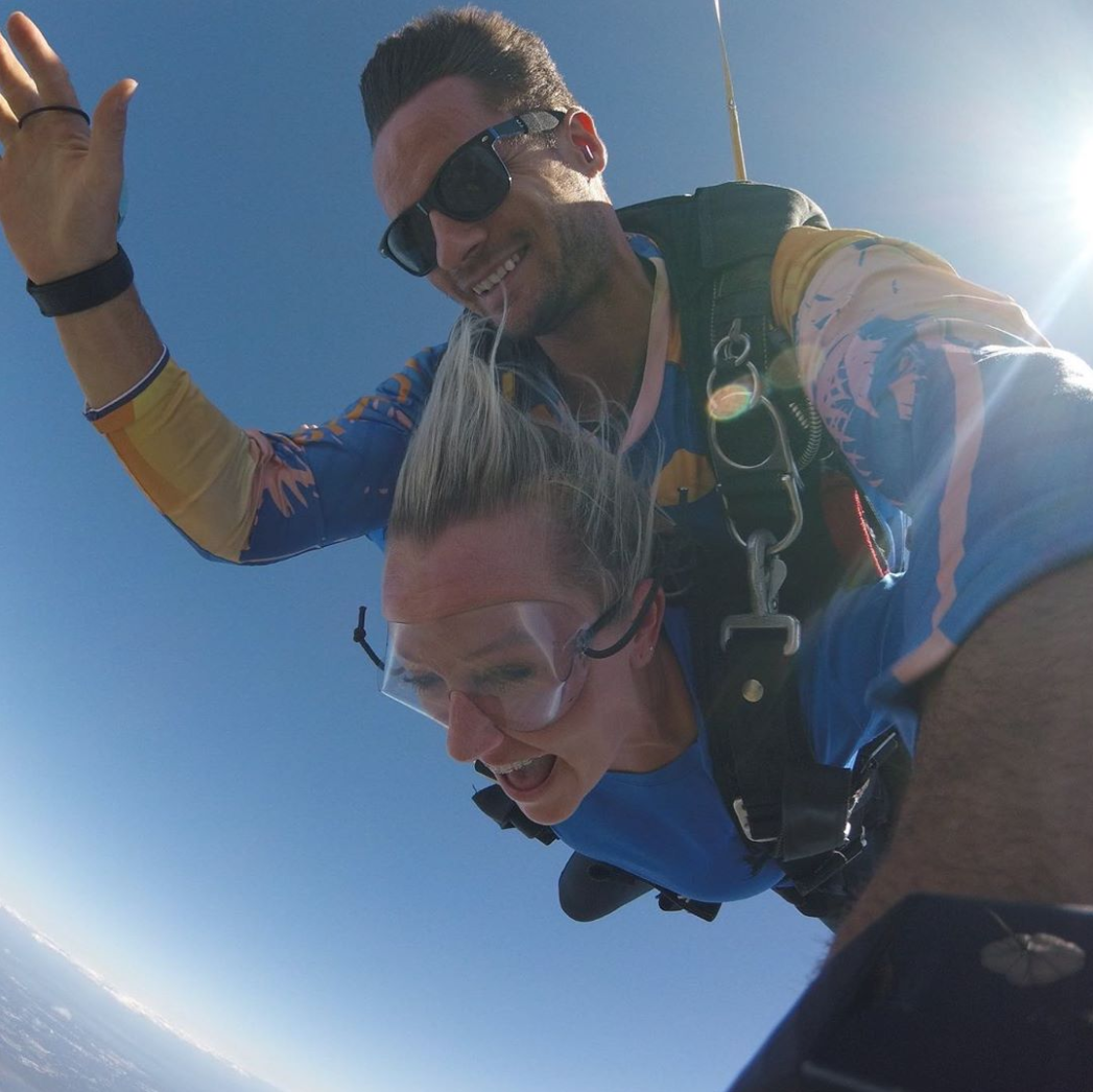 Woman and tandem skydiving instructor free falling near St. Louis Missouri