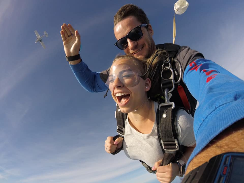 Woman smiling as she finishes free fall with parachute and plane behind her at Skydive St Louis near Chicago