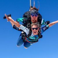 Women tandem skydiving with arms out surrounded by blue skies.