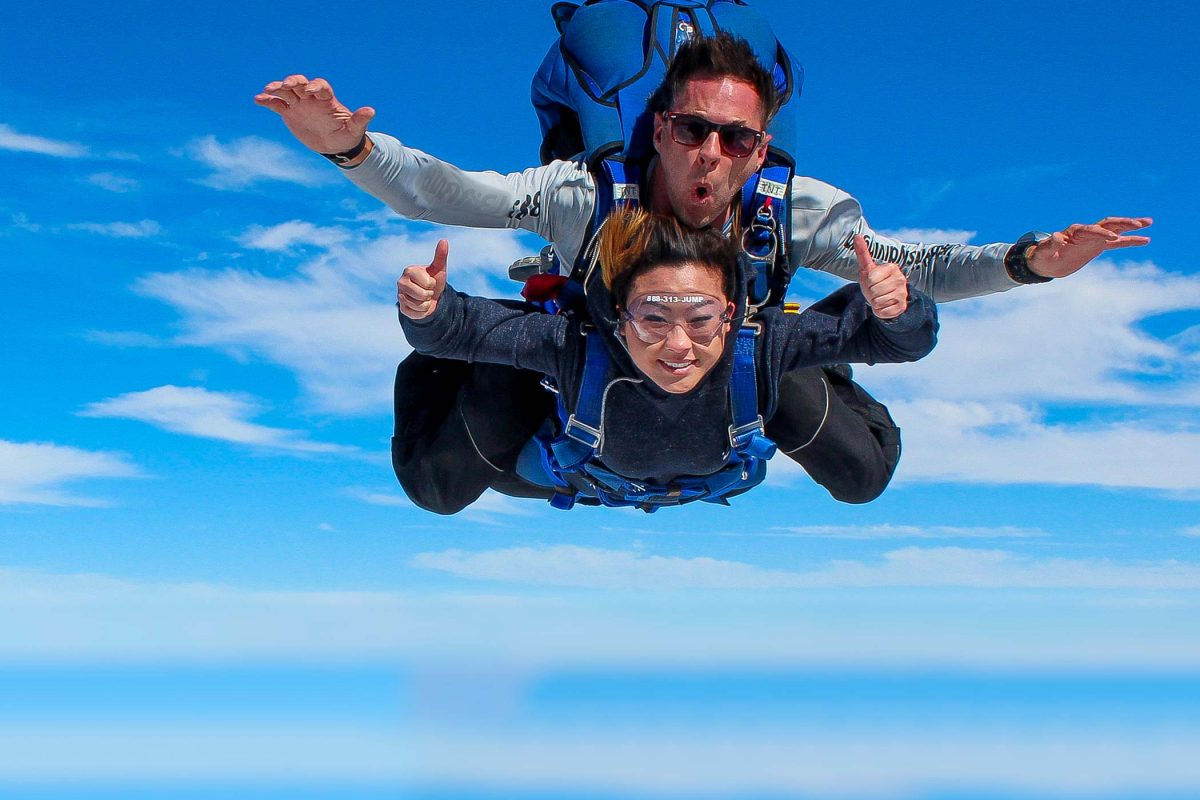 Women tandem skydiving while giving thumbs up with a blue harness on.