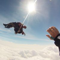 Tandem instructor and student in free fall above the clouds.
