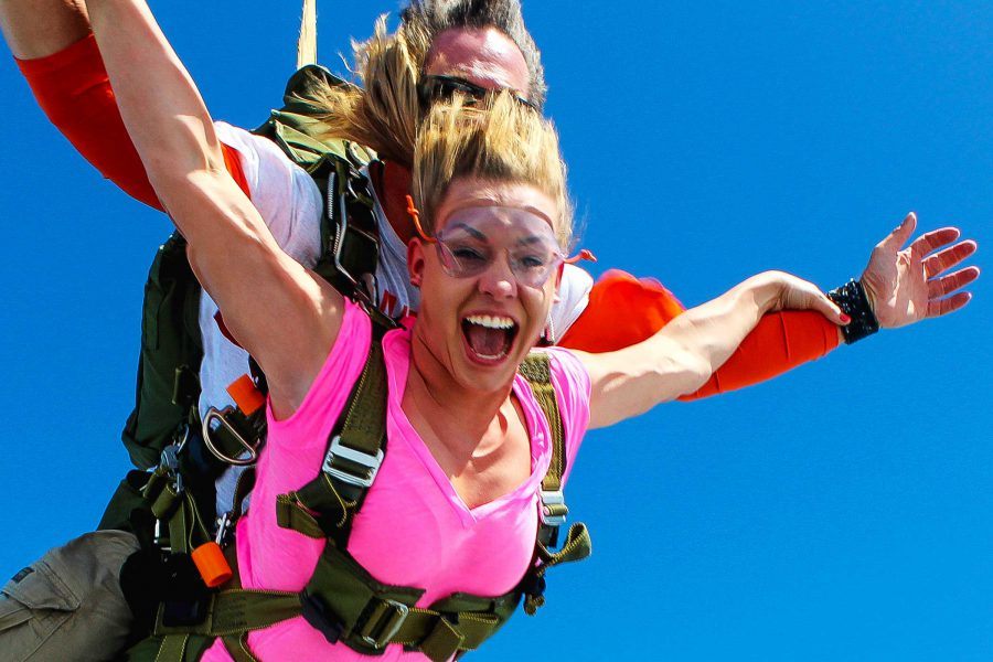 Women in pink shirt tandem skydiving with look of sheer excitement on her face.
