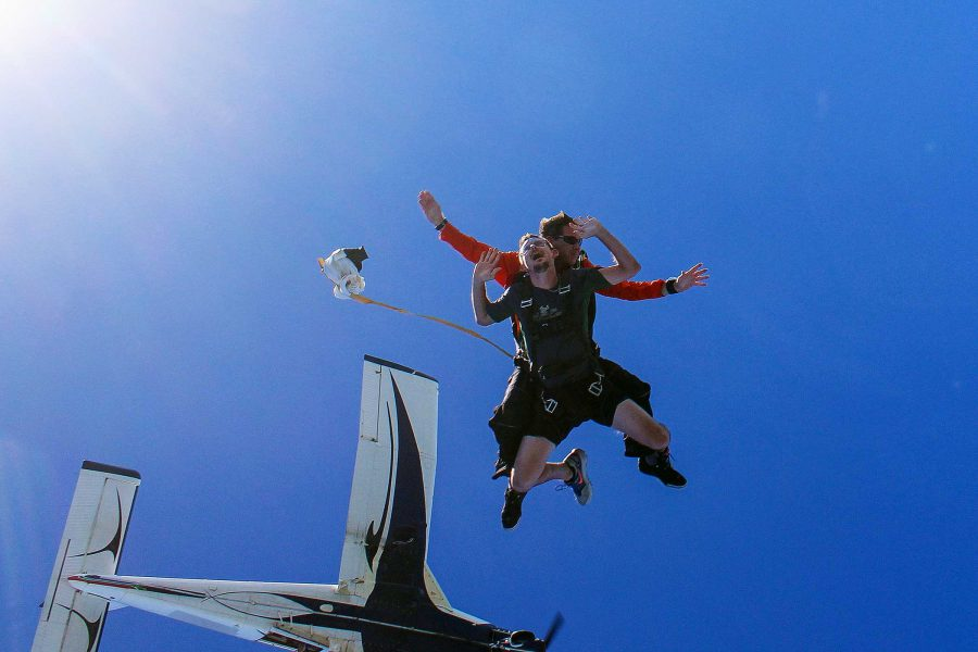 Instructor and student skydiving with black and white plane behind them.