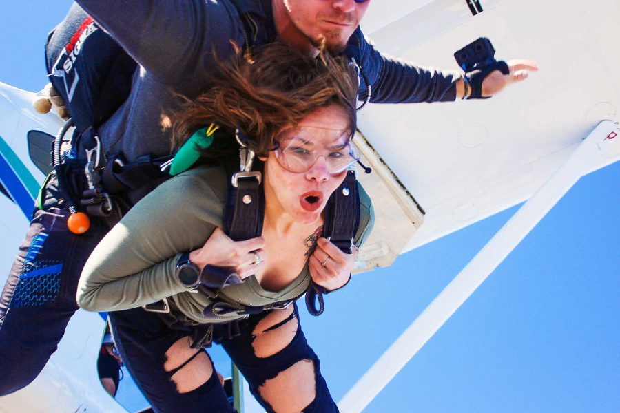 Tandem student taking the leap out of the Skydive STL airplane with a look of excitement