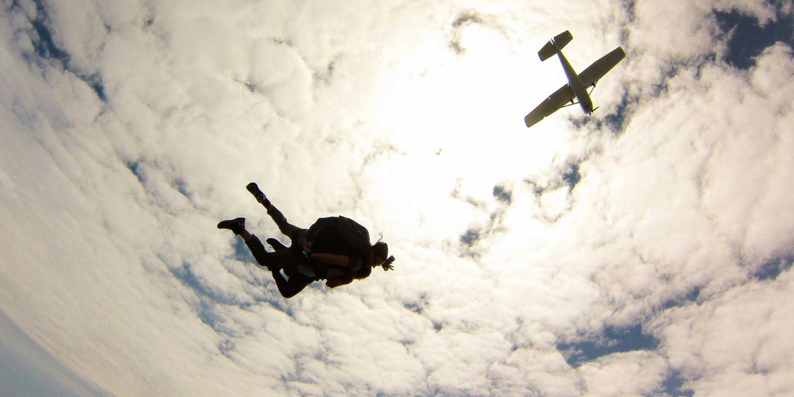 Tandem skydivers under the clouds are within the skydiving weight limit
