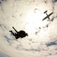 Tandem instructor and student in free fall with clouds and airplane above them