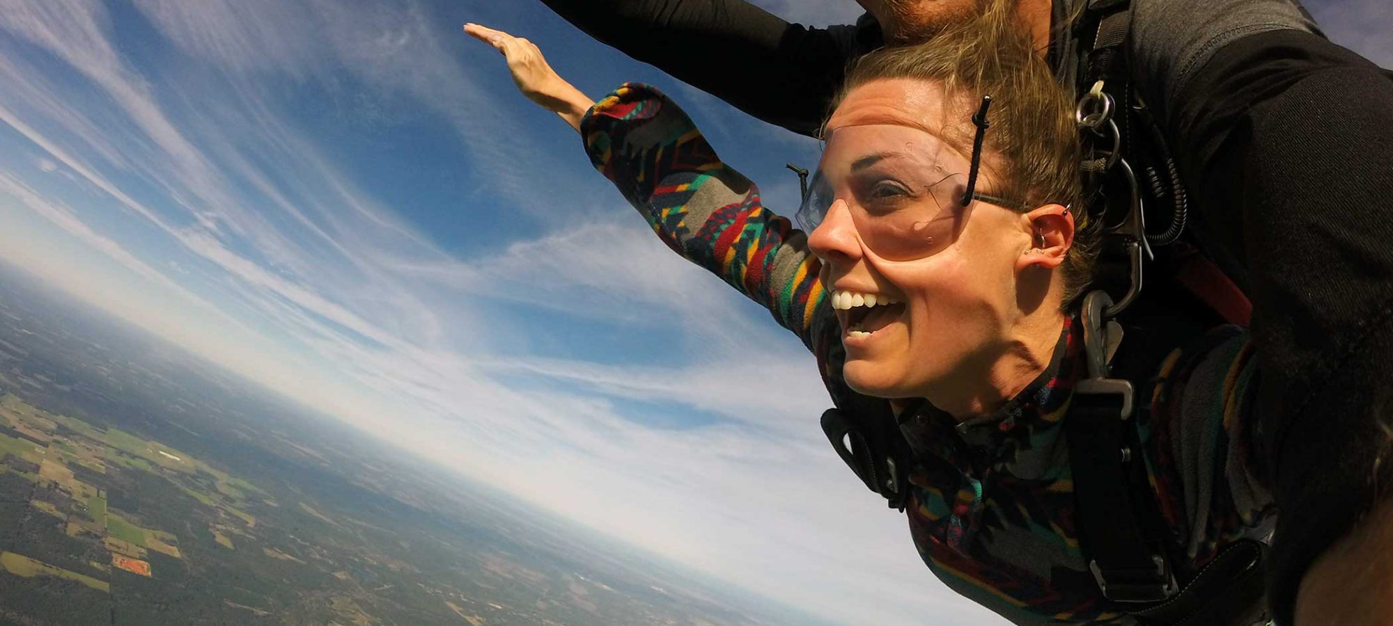 Women and tandem instructor smiling while skydiving