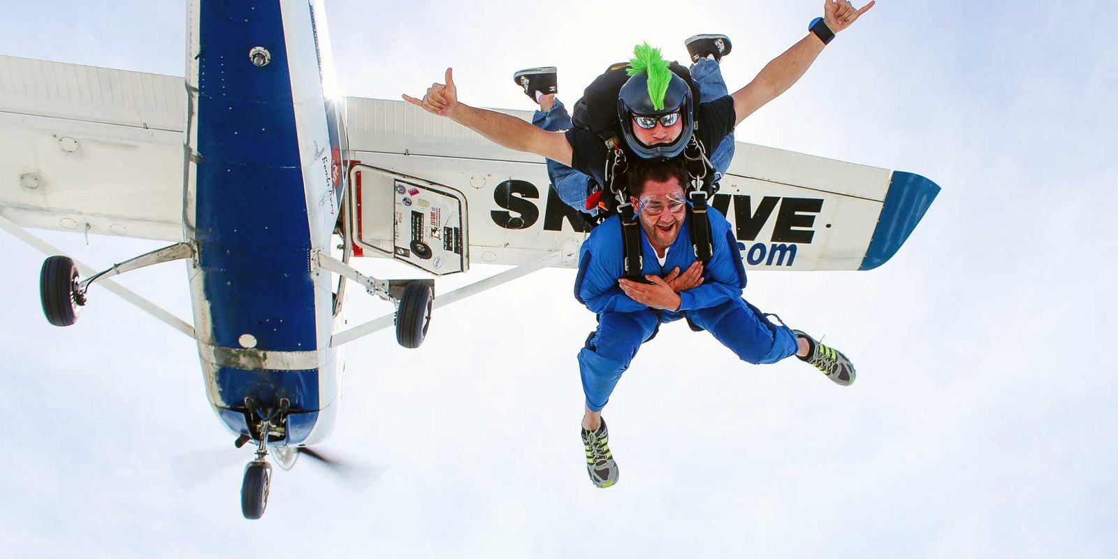 Tandem instructor with green mohawk helmet and student free falling with plane behind them.