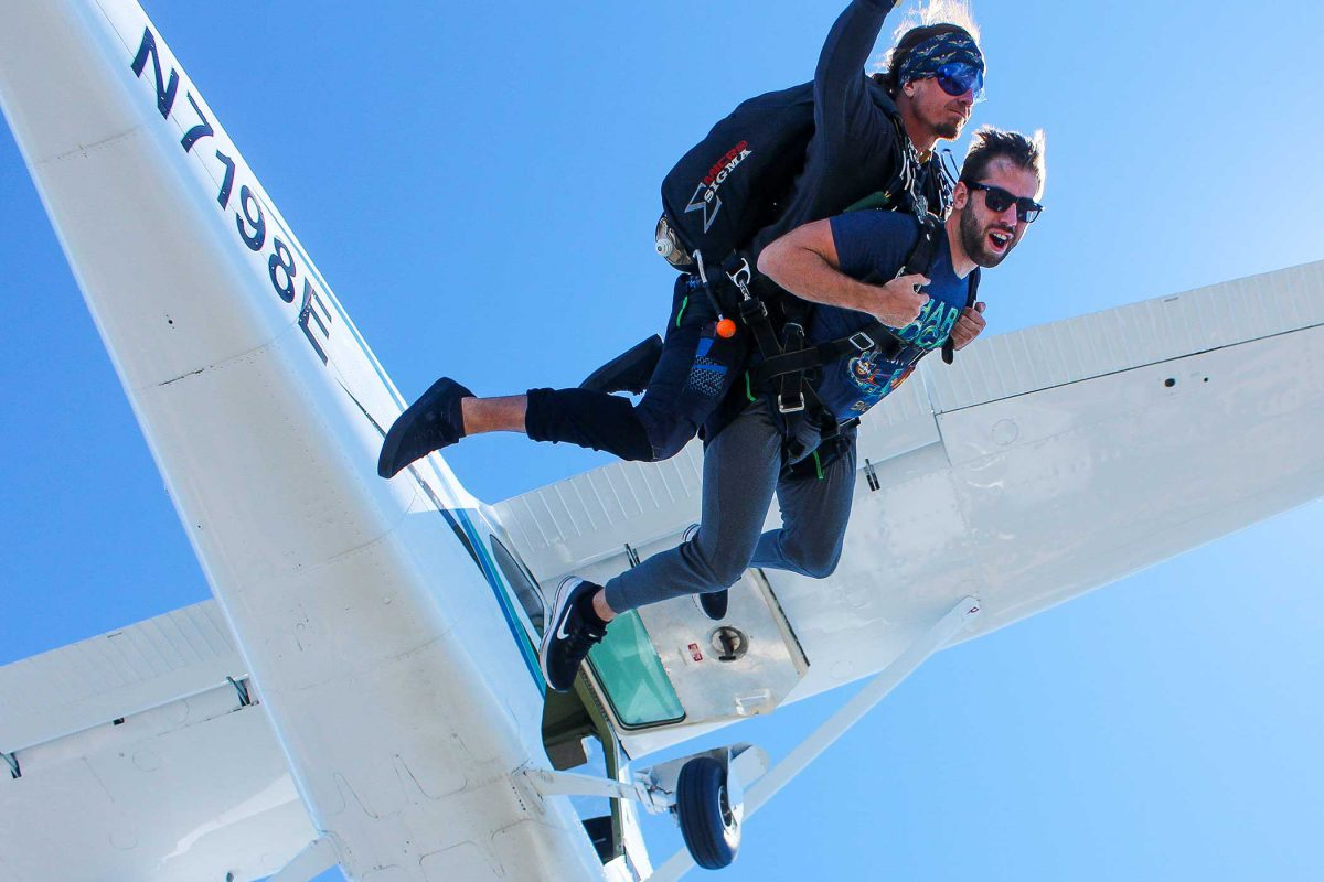 young man tandem skydiving with instructor with white plane behind them.