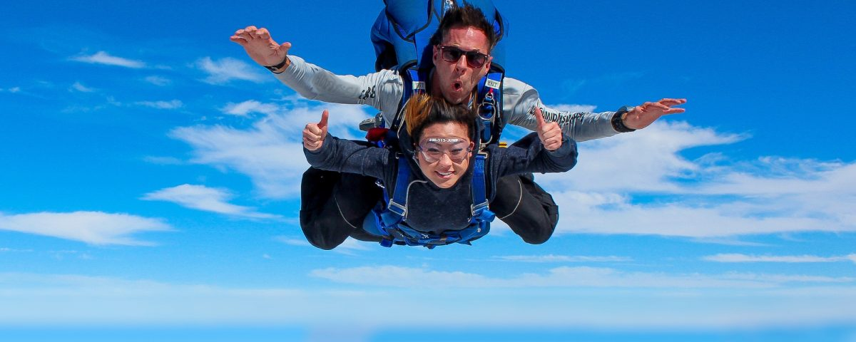 Women tandem skydiving while smiling and giving thumbs up.