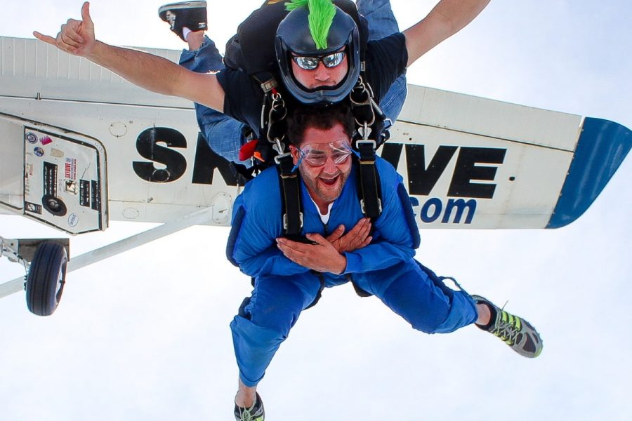 male tandem student smiles in freefall with arms crossed at his chest
