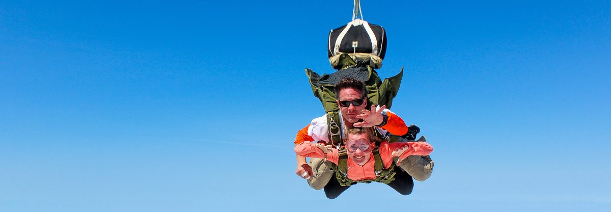 A woman tandem skydiving in St. Louis with an instructor