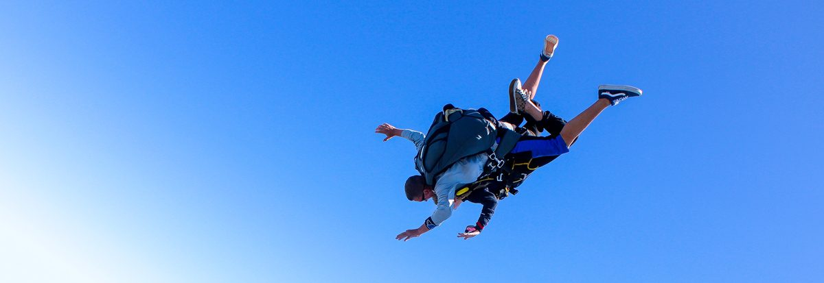 A man skydiving over St. Louis with a tandem skydiving instructor
