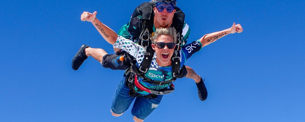 woman gives thumbs up in freefall with #survivor #strong written on each arm