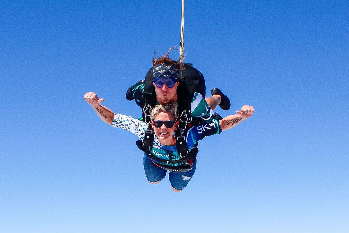 woman smiles in skydiving freefall against blue sky