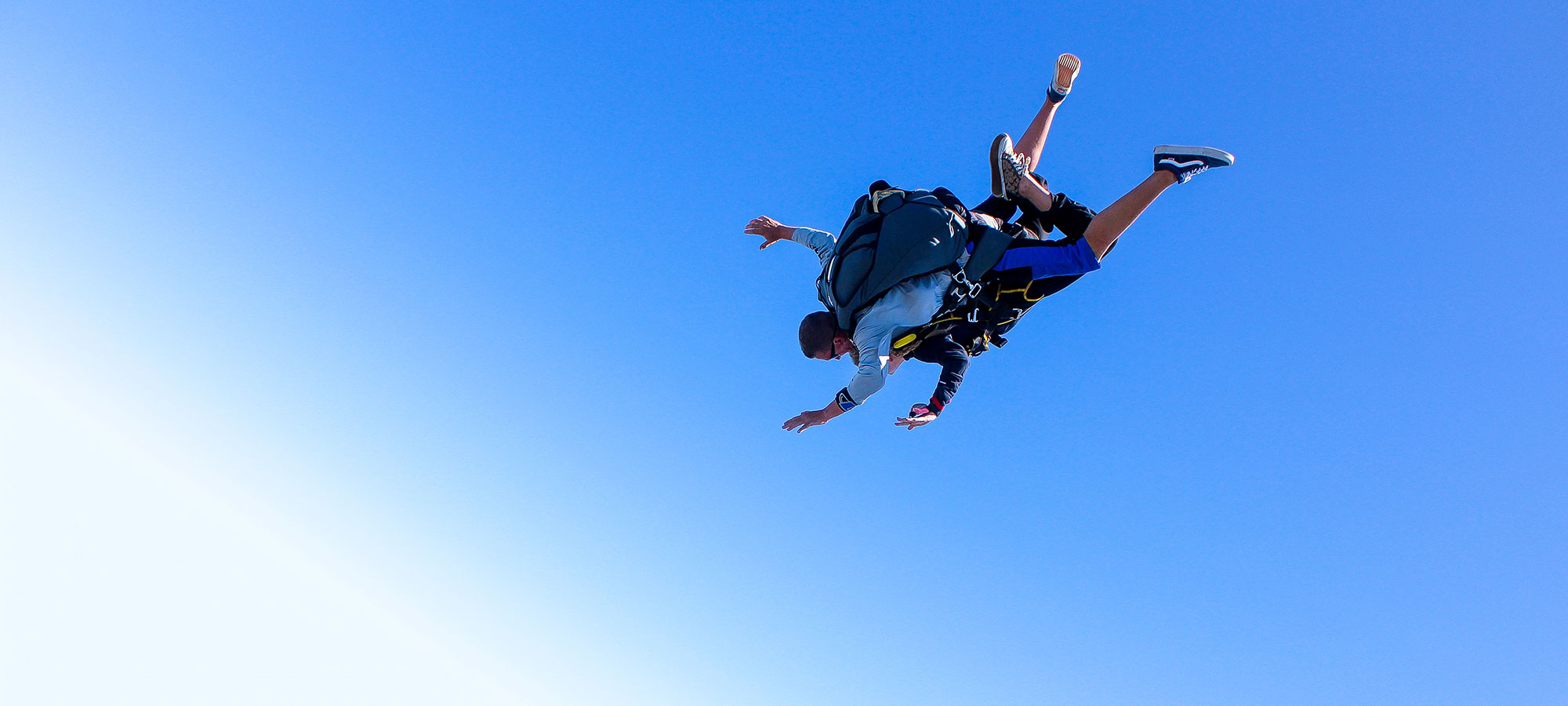 Tandem instructor and student in free fall with bright blue sky in the background.
