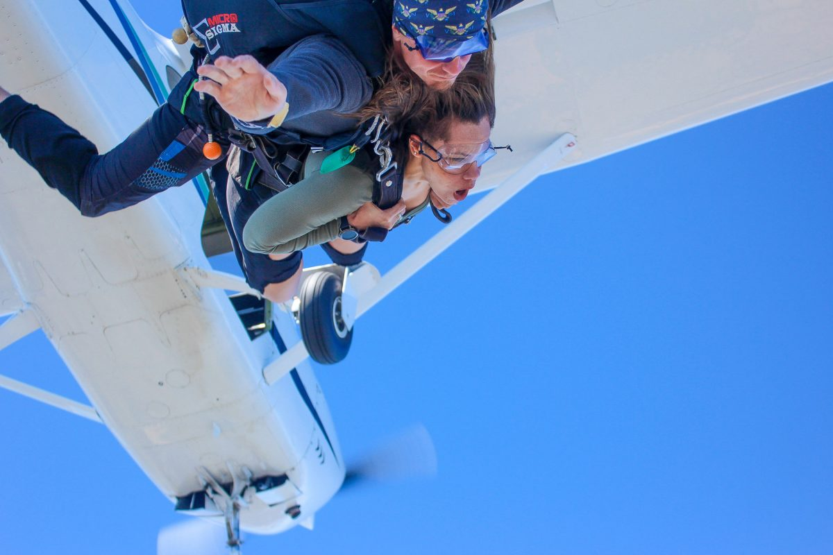 Women free falling with tandem instructor with Skydive STL airplane in the background.