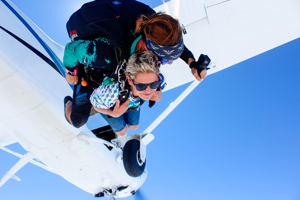 Women with short blond hair tandem skydiving with look of joy and calmness.
