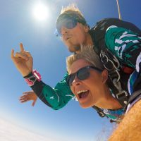 Women and instructor skydiving with looks of excitement and joy surrounded by blue skies over St. Louis, Missouri