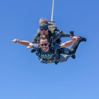 Tandem instructor and male student skydiving with looks of excitement.