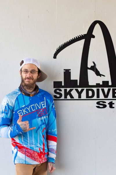 noah skydive stl instructor standing with shocka hand signal in jersey shirt smiling in front of white wall
