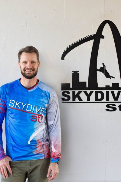 lee skydive stl manager wearing blue shirt and parachute in front of white wall while smiling