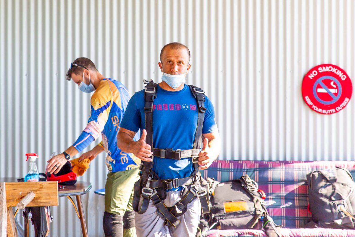 Skydiver giving thumbs up while preparing his parachute at Skydive St Louis