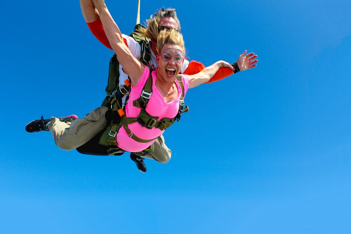 Women wearing pink shirt tandem skydiving with look of sheer excitement.